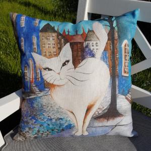 Designat kuddfodral i linne. Kattmotiv av vit katt mot blå stad.